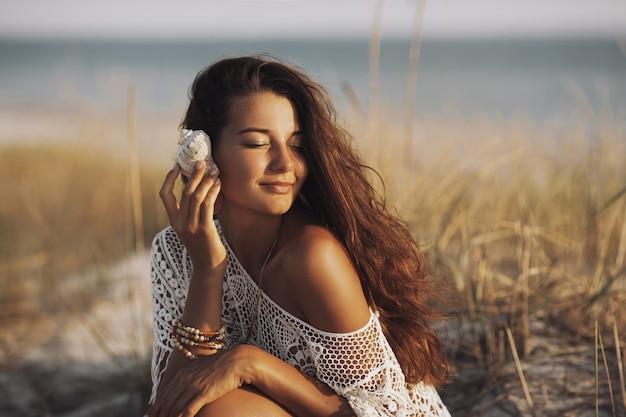 Kobieta z muszla na plaży podczas wakacji
