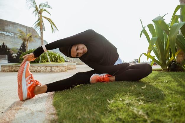 Kobieta z muzułmańskim sportem jest ubranym rozciąganie