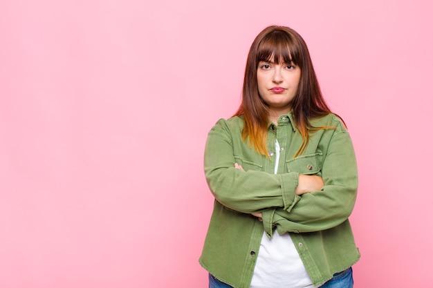 Kobieta z nadwagą czuje się niezadowolona i rozczarowana, wygląda na poważną, zirytowaną i wściekłą ze skrzyżowanymi rękami