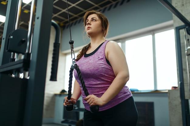 Kobieta z nadwagą robi ćwiczenia rozciągające w siłowni, aktywny trening. otyła kobieta zmaga się z nadwagą, trening aerobowy z otyłością, klub sportowy