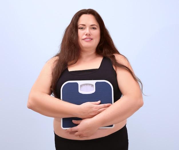 Kobieta z nadwagą trzyma wagę