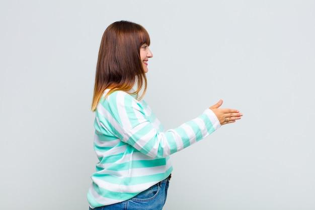 Kobieta z nadwagą uśmiecha się, wita i oferuje uścisk dłoni, aby sfinalizować udaną transakcję, koncepcja współpracy