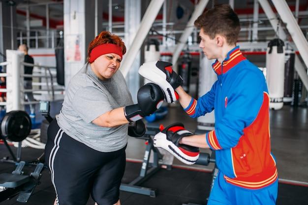 Kobieta z nadwagą w rękawiczkach bokserskich z instruktorem w siłowni.
