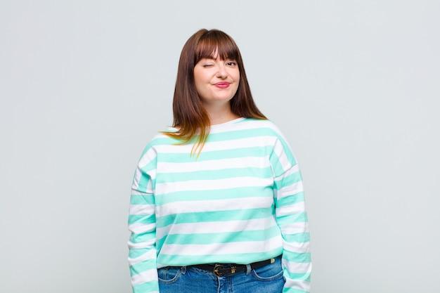 Kobieta z nadwagą wyglądająca wesoło i przyjaźnie, uśmiechnięta i mrugająca okiem z pozytywnym nastawieniem