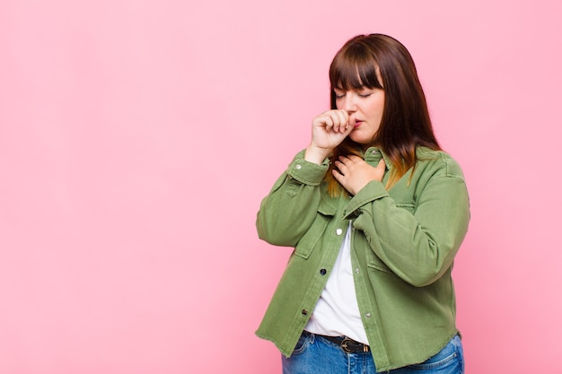 Kobieta z nadwagą źle się czuje z bólem gardła i objawami grypy, kaszle z zakrytymi ustami