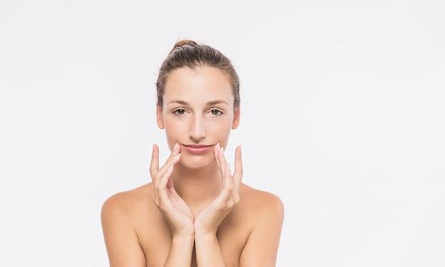 Kobieta z nagie ramiona dotykania twarzy