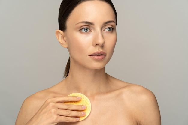 Kobieta z nagim makijażem i odkrytymi ramionami, myjąca ciało gąbką złuszczającą po prysznicu