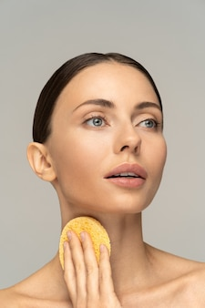 Kobieta z nagim makijażem i odsłoniętymi ramionami czyszcząca szyję izolowaną gąbką złuszczającą
