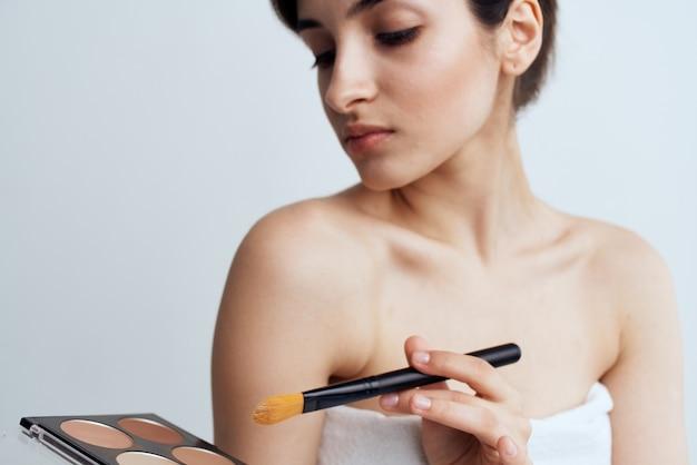 Kobieta z nagimi ramionami kosmetyki nakładające makijaż na pielęgnację twarzy