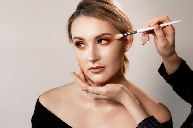 Kobieta z nagimi ramionami pozuje na lekkim studiu. ręce charakteryzatora korygują makijaż specjalnym pędzlem. profesjonalny makijaż