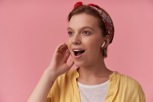 Kobieta z naturalnym makijażem ubrana w białą koszulkę i żółtą koszulę i czerwoną bandanę, patrząc na bok zaskoczony, uśmiechnięty na różowej ścianie