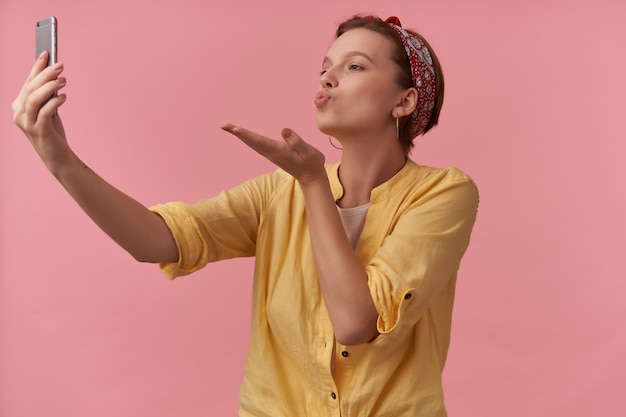 Kobieta z naturalnym makijażem ubrana w stylowy letni strój żółta koszula i czerwona bandana emocja flirtująca kochająca i wysyłająca pocałunek z powietrza zrób autoportret na różowo
