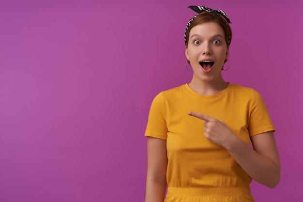 Kobieta z naturalnym makijażem ubrana w żółtą koszulkę i czarną bandanę emocja wow patrząc na ciebie szczęśliwy pokaz w lewo wskazujący palec ciekawy na bok na fioletowej ścianie