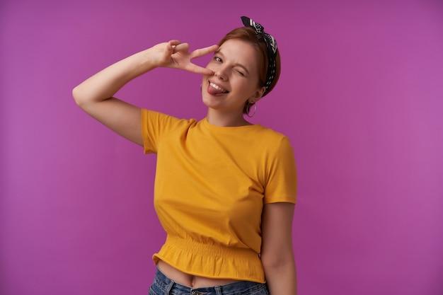 Kobieta z naturalnym makijażem ubrana w żółtą modną bluzkę i czarną chustkę pozująca na fioletowej ścianie pokazuje dwa palce uśmiechające się do ciebie emocje flirt mrugnięcie radość zabawny