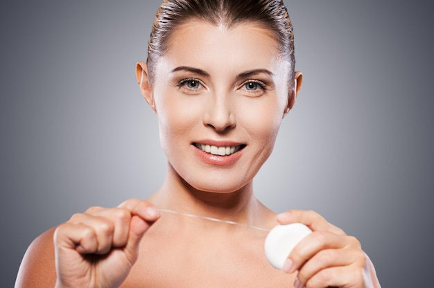 Kobieta z nicią dentystyczną. piękna dojrzała kobieta trzyma nić dentystyczną i uśmiecha się do kamery stojąc na szarym tle