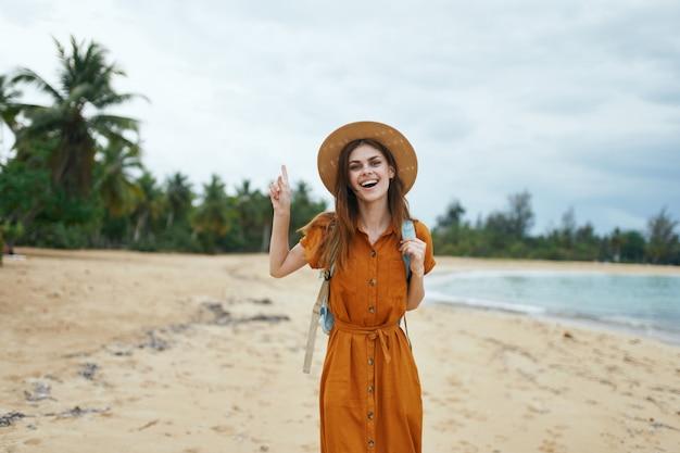 Kobieta z niebieskim plecakiem w żółtej sukience i kapeluszu idzie oceanem wzdłuż piasku z palmami