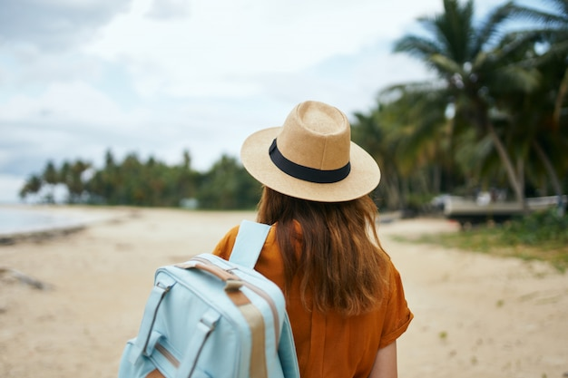 Kobieta z niebieskim plecakiem w żółtej sukience i kapeluszu idzie wzdłuż oceanu wzdłuż piasku z palmami