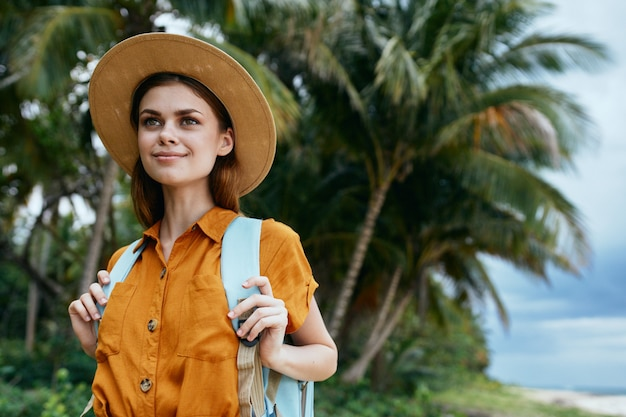 Kobieta z niebieskim plecakiem w żółtej sukience i kapeluszu idzie wzdłuż piasku z palmami