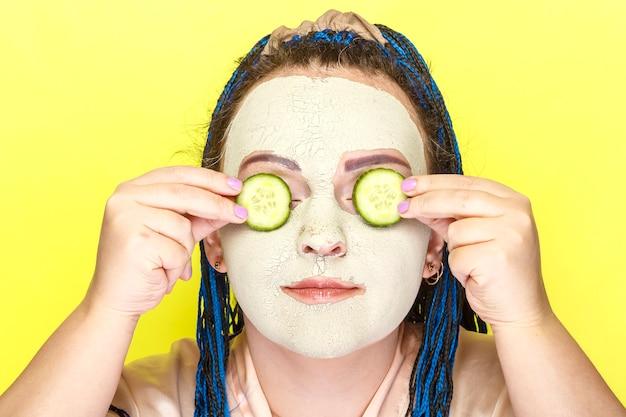 Kobieta z niebieskimi afro warkoczami twarz w zamarzniętej masce z zielonej glinki z kawałkami ogórków przed oczami na żółtej powierzchni