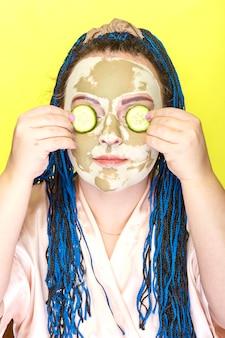 Kobieta z niebieskimi afro warkoczykami, twarz w masce z zielonej gliny z ogórkowymi kółkami na oczach na żółtej ścianie