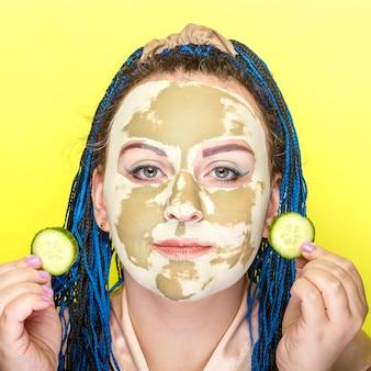 Kobieta z niebieskimi warkoczami afro twarz w masce wykonanej z zielonej gliny z kręgami ogórka w dłoniach na żółtej ścianie