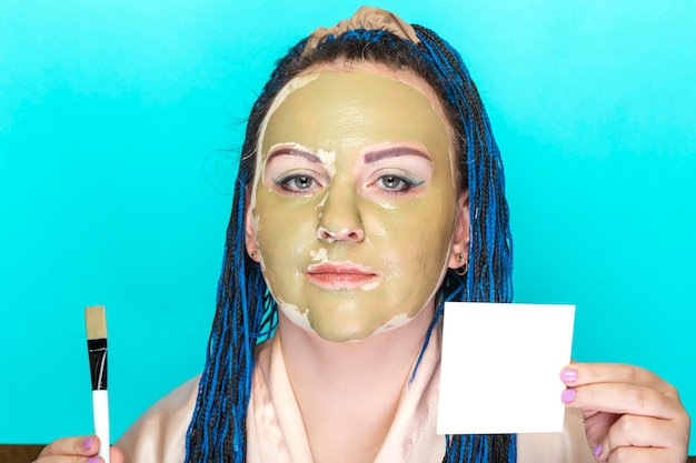 Kobieta z niebieskimi warkoczami afro twarz w masce z zielonej gliny na niebieskiej powierzchni z pędzelkiem w dłoniach