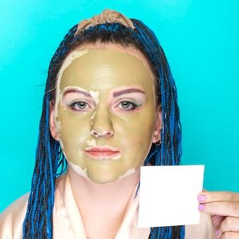 Kobieta z niebieskimi warkoczami afro twarz w masce z zielonej gliny na niebieskiej powierzchni z wizytówką w dłoniach