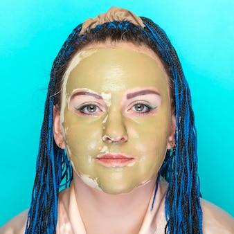 Kobieta z niebieskimi warkoczami afro twarz w masce z zielonej gliny na niebieskiej powierzchni