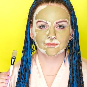 Kobieta z niebieskimi warkoczami afro twarz w masce z zielonej gliny na żółtej powierzchni z pędzelkiem w dłoniach