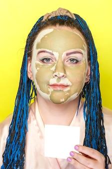 Kobieta z niebieskimi warkoczami afro twarz w masce z zielonej gliny na żółtej powierzchni z wizytówką w dłoniach