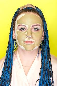 Kobieta z niebieskimi warkoczami afro twarz w masce z zielonej gliny na żółtej powierzchni