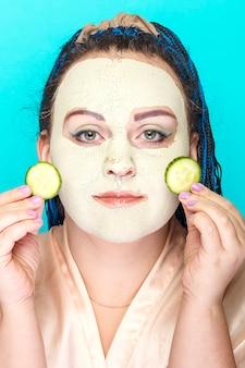 Kobieta z niebieskimi warkoczami afro twarz w zamarzniętej masce z zielonej glinki z kawałkami ogórka w dłoniach.