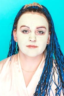 Kobieta z niebieskimi warkoczami afro twarz w zamarzniętej masce z zielonej glinki.