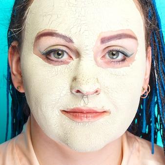 Kobieta z niebieskimi warkoczami afro twarz w zamarzniętej masce zielonej gliny twarzy zbliżenie