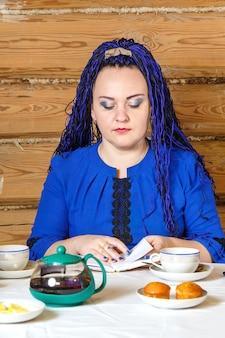 Kobieta z niebieskimi warkoczami afro w domowym biurze przy komputerze działa. zdjęcie pionowe