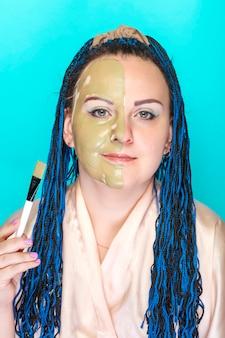 Kobieta z niebieskimi warkoczami afro, z połową twarzy w masce z zielonej glinki na niebieskiej powierzchni, trzyma pędzel