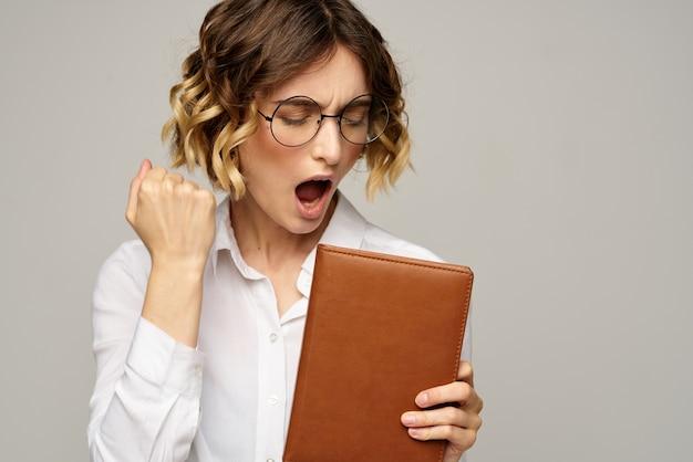 Kobieta z notatnika w rękach biznes pracy okulary beżowe fryzury.