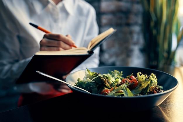 Kobieta z notatnikiem w pobliżu okna i sałatką w talerzu pomidory świeże warzywa