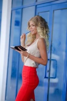 Kobieta z notatnikiem w rękach modelka ubrana w obcisłe ubrania biznesowe podejmuje decyzje biznesowe
