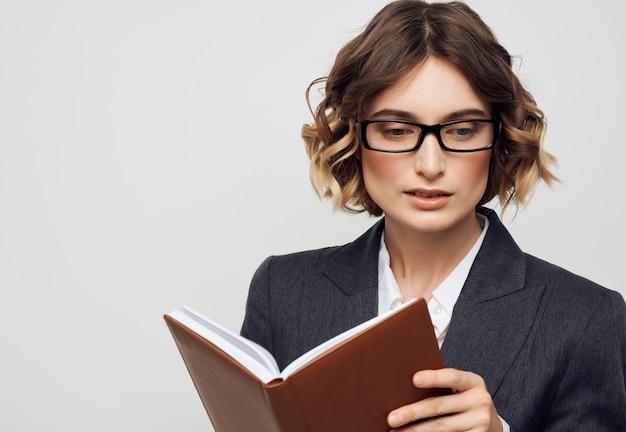 Kobieta z notebookiem okulary w ręku na białym tle. zdjęcie wysokiej jakości
