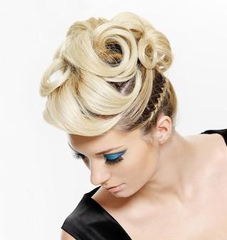 Kobieta z nowoczesną fryzurę i niebieski makijaż oczu na białym tle. wysoki kąt widzenia