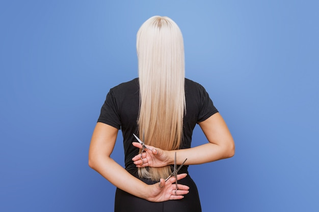 Kobieta z nożyczkami odchyla się i obcina długie blond włosy. koncepcja profesjonalnego fryzjera i pielęgnacji włosów