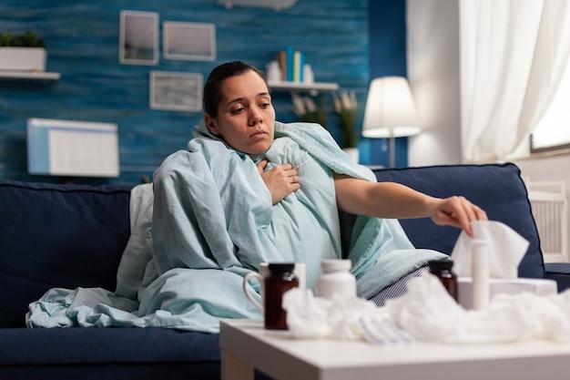Kobieta z objawami grypy siedzi chora w domu