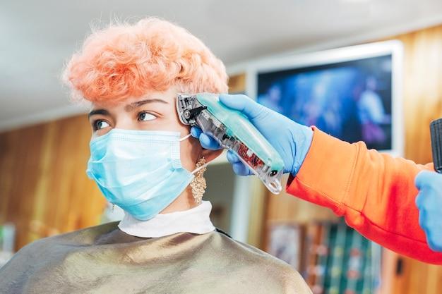 Kobieta z ochronną maskę medyczną w salonie fryzjerskim. sklep fryzjerski otwarty dla publiczności ze środkami bezpieczeństwa, aby uniknąć infekcji koronawirusem.
