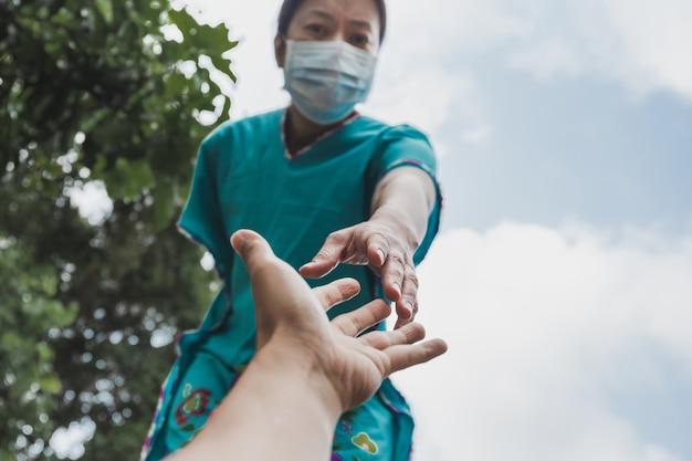 Kobieta z ochronnym maks wyciąga rękę, by pomóc