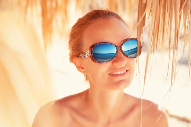 Kobieta z odbiciem morza w okulary przeciwsłoneczne
