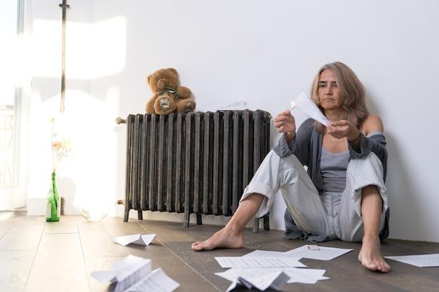 Kobieta z oderwaną miną siedzi na podłodze swojego mieszkania i podpala samolot wykonany z papieru