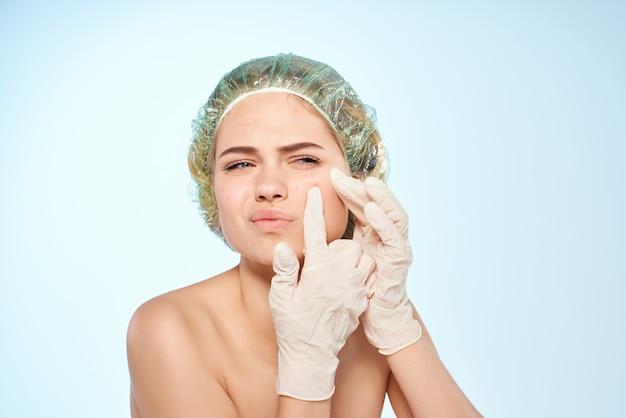 Kobieta z odkrytymi ramionami czepki pod prysznic wyciskają pryszcze na niebieskim tle twarzy