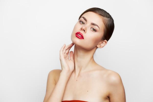 Kobieta z odkrytymi ramionami czysta skóra i czerwone usta elegancki styl jasny makijaż zbliżenie
