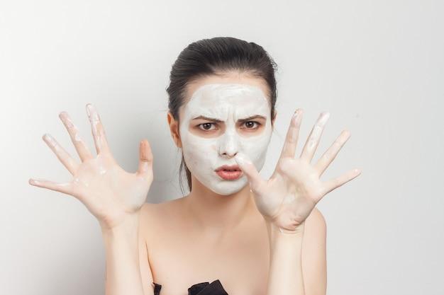 Kobieta z odkrytymi ramionami jest w ręku stosując kosmetyki do pielęgnacji skóry